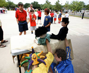 Photo - Jack Wagner, left, and Ryan Garcia run a puppet show during Tuesday's medieval fair at St. Elizabeth Ann Seton Catholic School in Edmond.  Photos by Sarah Phipps, The Oklahoman