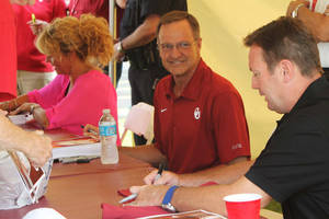 Photo - From left, OU coaches Sherri Coale, Lon Kruger, and Bob Stoops sign autographs during the Sooner Caravan in Tulsa on Wednesday. Photo by JAMES GIBBARD, Tulsa World