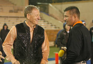 photo - WEATHER DELAY: Oklahoma State&#039;s Mike Holder and head coach Mike Gundy talk on the field during rain delay at a college football game between the Oklahoma State University Cowboys (OSU) and the University of Tulsa Golden Hurricane (TU) at H.A. Chapman Stadium in Tulsa, Okla., Saturday, Sept. 17, 2011. Photo by Sarah Phipps, The Oklahoman  ORG XMIT: KOD