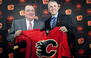 photo -   New Calgary Flames' head coach Bob Hartley, right, holds up a jersey with general manager Jay Feaster following an NHL hockey news conference in Calgary, Alberta, Thursday, May 31, 2012. (AP Photo/The Canadian Press, Jeff McIntosh)