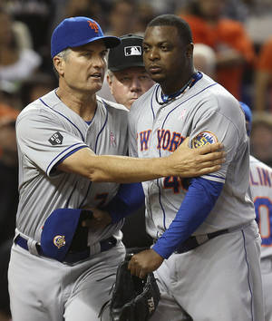 photo -   As New York Mets manager Terry Collins, background right, argues with home plate umpire Todd Tichenor (obscured), Mets bench coach Bob Geren, left, pushes Frank Francisco away during the ninth inning of a baseball game against the Miami Marlins in Miami, Sunday, May 13, 2012. The Marlins defeated the Mets 8-4. (AP Photo/J Pat Carter)  