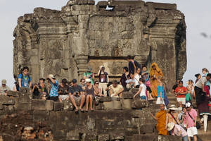 Photo -   FILE - In this file May 11, 2011, tourists gather on the top of the 10th century temple Bakheng in the Angkor Wat complex near Siem Reap, Cambodia, to view the setting sun. Prime Minister Hun Sen says Cambodia can earn $5 billion a year from tourists by more than doubling foreign visitors to 7 million by 2020. Hun Sen told a tourism seminar Thursday, Sept. 20, 2012, that Cambodia would need to improve the quality of services and infrastructure for tourists and strengthen laws safeguarding them to achieve the goal. (AP Photo/David Longstreath, File)