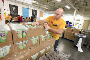 Photo -      Love's employee Aaron Ritchal opens boxes of food to be sorted Friday at the Regional Food Bank of Oklahoma.  <strong>PAUL B. SOUTHERLAND -  PAUL B. SOUTHERLAND </strong>