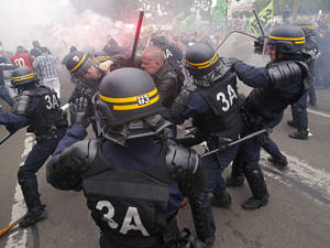 Photo - French riot police clash with a striking train workers, during a protest over a bill to reform the state-run railway system in Paris, Tuesday, June 17, 2014. A weeklong strike by rail workers has caused one of the worst disruptions to the country's rail network in years and is heating up as the reform bill goes to the lower house of Parliament for debate Tuesday. (AP Photo/Michel Euler)