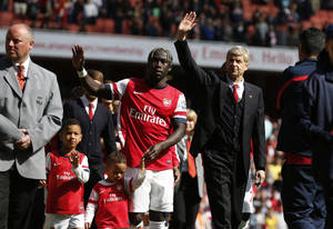 Photo - Arsenal's manager Arsene Wenger, center right, and Bacary Sagna, center left, wave to the supporters as the team parade around the stadium in their last home match of the season, after their English Premier League soccer match against West Bromwich Albion at Emirates Stadium in London, Sunday, May 4, 2014. (AP Photo/Sang Tan)