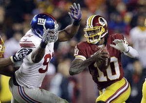 Photo - New York Giants defensive end Justin Tuck, left, tackles Washington Redskins quarterback Robert Griffin III (10) during the second half of an NFL football game Sunday, Dec. 1, 2013, in Landover, Md. (AP Photo/Patrick Semansky)