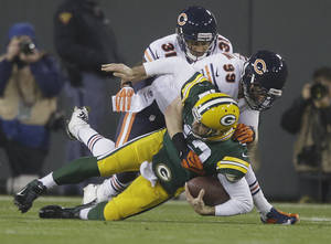 Photo - Green Bay Packers quarterback Aaron Rodgers is sacked by Chicago Bears' Shea McClellin (99) and Isaiah Frey (31) during the first half of an NFL football game Monday, Nov. 4, 2013, in Green Bay, Wis. Rodgers left the game after the play. (AP Photo/Jeffrey Phelps)