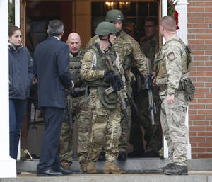 Photo - Officials exit St. Rose of Lima Roman Catholic Church while responding to a bomb threat, Sunday, Dec. 16, 2012, in Newtown, Conn. Worshippers hurriedly left the church Sunday, not far from where a gunman opened fire Friday inside the Sandy Hook Elementary School in Newtown. (AP Photo/Julio Cortez)