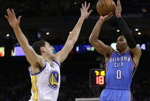 Photo - Oklahoma City Thunder's Russell Westbrook, right, shoots over Golden State Warriors' Klay Thompson (11) during the first half of an NBA basketball game Thursday, Nov. 14, 2013, in Oakland, Calif. (AP Photo/Ben Margot)