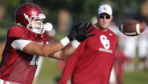 Photo - Former Oklahoma quarterback and now tight end Blake Bell reaches to catch a pass during an NCAA college football team practice in Norman, Okla., Tuesday, Aug. 5. 2014. (AP Photo/Sue Ogrocki)