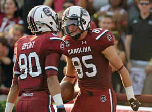 Photo - South Carolina wide receiver Kane Whitehurst (85) celebrates with teammate wide receiver K.J. Brent (80) after scoring a touchdown during the first half of an NCAA college football game against North Carolina, Thursday, Aug. 29, 2013, in Columbia, S.C. (AP Photo/Stephen Morton)