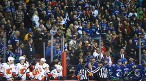 Photo - Referees get in the way of Vancouver Canucks head coach John Tortorella as he shouts at the Calgary Flames bench during first-period NHL hockey action in Vancouver, British Columbia, Saturday, Jan. 18, 2014. (AP Photo/The Canadian Press, Jonathan Hayward)