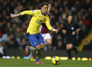 Photo - Arsenal's Mesut Ozil takes the ball forward during the English Premier League soccer match between Aston Villa and Arsenal at Villa Park stadium in Birmingham, England, Monday, Jan. 13, 2014. (AP Photo/Kirsty Wigglesworth)