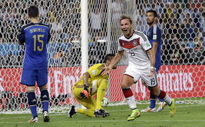 Photo - Germany's Mario Goetze celebrates after scoring the opening goal during the World Cup final soccer match between Germany and Argentina at the Maracana Stadium in Rio de Janeiro, Brazil, Sunday, July 13, 2014. (AP Photo/Victor R. Caivano)
