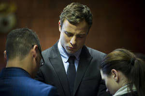 Photo - FILE - In this file photo taken on Monday, Aug. 19, 2013, Oscar Pistorius, center, cries as he prays with his sister Aimee and brother Carl in the magistrates court in Pretoria, South Africa. Oscar Pistorius was served with new indictment papers Wednesday, Nov. 20,  containing two extra charges believed to allege that he recklessly shot his gun out the open sunroof of a car last year and fired someone else's handgun at a restaurant weeks before he killed girlfriend Reeva Steenkamp. (AP Photo/File)