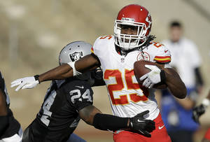 Photo - Kansas City Chiefs running back Jamaal Charles (25) runs against Oakland Raiders cornerback Charles Woodson during the second quarter of an NFL football game in Oakland, Calif., Sunday, Dec. 15, 2013. (AP Photo/Ben Margot)