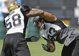 Photo - Jacksonville Jaguars defensive tackle Tyson Alualu, right, and defensive end Jason Babin (58) go through a drill during NFL football training camp, Monday, July 29, 2013, in Jacksonville, Fla. (AP Photo/John Raoux)