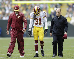 Photo - Washington Redskins' Brandon Meriweather is helped off the field during the first half of an NFL football game against the Green Bay Packers Sunday, Sept. 15, 2013, in Green Bay, Wis. (AP Photo/Tom Lynn)