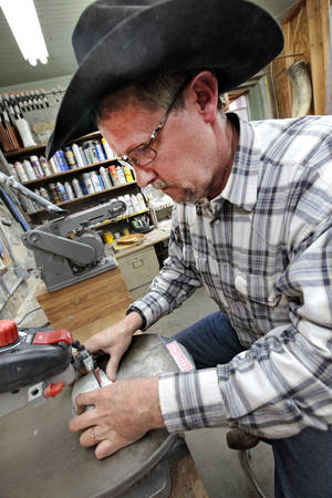 Photo - Ranch foreman James Coldren works on a  belt buckle made from cattle horns on a ranch near Foraker.  <strong>David McDaniel - The Oklahoman</strong>
