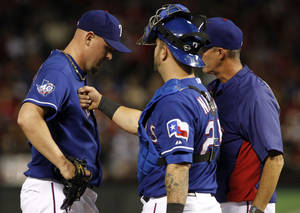 Photo -   Texas Rangers starting pitcher Matt Harrison, left, takes a tap to the chest from catcher Mike Napoli as pitching coach Mike Maddux, right, visits the mound in the fifth inning of a baseball game against the Tampa Bay Rays, Friday, April 27, 2012, in Arlington, Texas. (AP Photo/Tony Gutierrez)