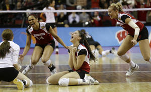 Photo - Wisconsin's Lauren Carlini, center, celebrates with teammates after they beat Texas in an NCAA women's volleyball tournament semifinal Thursday, Dec. 19, 2013, in Seattle. (AP Photo/Elaine Thompson)