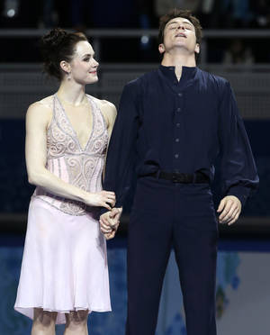 Photo - Tessa Virtue and Scott Moir of Canada react after placing second during the flower ceremony ice dance free dance figure skating finals at the Iceberg Skating Palace during the 2014 Winter Olympics, Monday, Feb. 17, 2014, in Sochi, Russia. (AP Photo/Darron Cummings)