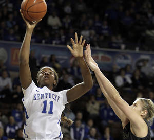Photo - Kentucky's DeNesha Stallworth (11) shoots near Missouri's Morgan Stock during the first half of an NCAA college basketball game, Sunday, Jan. 12, 2014, in Lexington, Ky. (AP Photo/James Crisp)