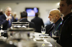 Photo - Afghan President Hamid Karzai, right, waits to order a coffee in the presidential lounge before the opening ceremony of the 2014 Winter Olympics, Friday, Feb. 7, 2014, in Sochi, Russia. (AP Photo/David Goldman, Pool)