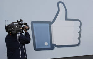 photo -   A television photographer shoots the Like sign outside of Facebook headquarters in Menlo Park, Calif., Friday, May 18, 2012. Facebook CEO Mark Zuckerberg symbolically opened trading on the Nasdaq stock market inside Facebook headquarters in Menlo Park. Facebook stock is starting trading today, available to the general public for the first time. The social networking site, which was started in a college dorm room eight years ago, would be valued at more than $100 billion according to the price set for shares ahead of today's trading. (AP Photo/Paul Sakuma)