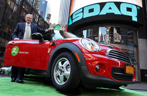 Photo - Zipcar Chairman and CEO Scott Griffith stands with a Mini Cooper before the opening bell at the Nasdaq Market Site in New York. AP Photo