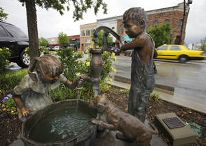 Photo - Puppy Love by Marianne Caroselli is one of the 157 statutes placed  downtown and in other areas of Edmond. PHOTO BY DAVID MCDANIEL, THE OKLAHOMAN. <strong>David McDaniel - The Oklahoman</strong>