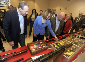 Photo - New York Attorney General Eric Schneiderman, left, former Arizona congresswoman Gabrielle Giffords, center, and her husband Mark Kelly tour the New EastCoast Arms Collectors Associates arms fair in Saratoga Springs, N.Y. on Sunday, Oct. 13, 2013. (AP Photo/Tim Roske, Pool)