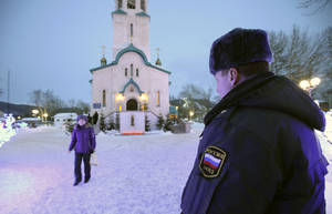 Photo - A policeman watches a believer leaving the Cathedral of the Resurrection of Christ in Yuzhno-Sakhalinsk on Sunday, Feb. 9, 2014. Law enforcement officers detained a man, who worked as a security guard, and were trying to determine why he attacked the Russian Orthodox cathedral in the city of Yuzhno-Sakhalinsk, the federal Investigative Committee said in a statement. A gunman opened fire Sunday in a cathedral on Russia's Sakhalin Island in the Pacific, killing a nun and a parishioner and wounding six others, investigators said. Concerns about security in Russia are especially high because of the Winter Olympics in Sochi, but there was no apparent connection to the games. Sakhalin Island is about 7,500 kilometers (more than 4,500 miles) from Sochi. (AP Photo/ Dmitriy Sindyakov)