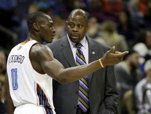 Photo - Charlotte Bobcats center Bismack Biyombo, left, talks with head coach Patrick Ewing in the first half of an NBA basketball game against the New York Knicks in Charlotte, N.C., Friday, Nov. 8, 2013. Ewing coached the team instead of Steve Clifford who was hospitalized. New York won 101-91. (AP Photo/Nell Redmond)
