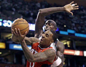 Photo -   Atlanta Hawks guard Jeff Teague, front, gets past Boston Celtics forward Kevin Garnett, who starts to swipe his arm on a block, during the second half of Game 3 of an NBA first-round playoff basketball series, Friday, May 4, 2012, in Boston. (AP Photo/Charles Krupa)