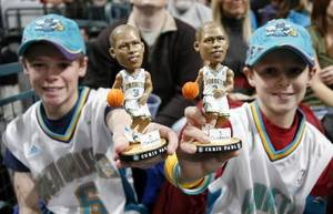 Photo - Hornets fans Josh Garbrecht, 11, left, and Jarret Garbrecht, 9, both of Edmond, Okla., show their Chris Paul bobblehead dolls during the NBA basketball game between the New Orleans/ Oklahoma City Hornets and the Orlando Magic at the Ford Center in Oklahoma City, Tuesday, Jan. 16, 2007. The Hornets gave away Chris Paul bobblehead dolls before the game. By Nate Billings