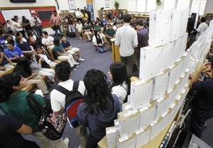 Photo - Students wait beside a pyramid of cell phones at Roosevelt Middle School in Oklahoma City, OK  before they receive the free phones, as the district rolls out a new free-minute incentive plan, Friday, Oct. 8, 2010. By Paul Hellstern, The Oklahoman ORG XMIT: KOD