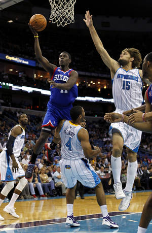 Photo -   Philadelphia 76ers point guard Jrue Holiday (11) drives to the basket as New Orleans Hornets shooting guard Xavier Henry (4) draws an offensive foul in the first half of an NBA basketball game in New Orleans, Wednesday, Nov. 7, 2012. (AP Photo/Gerald Herbert)