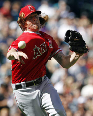 Photo -   Los Angeles Angels starting pitcher Jered Weaver throws to first after fielding a ground ball, that first knocked him down, from Seattle Mariners' Dustin Ackley in the fifth inning of a baseball game on Sunday, Sept. 2, 2012, in Seattle. Ackley singled on the play. (AP Photo/Elaine Thompson)