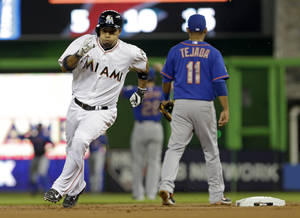 Photo - Miami Marlins' Rafael Furcal, left, rounds second base after hitting a triple against the New York Mets in the first inning of a baseball game in Miami, Friday, June 20, 2014. (AP Photo/Alan Diaz)