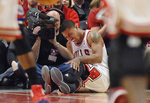 photo -   Chicago Bulls point guard Derrick Rose reats after injuring his leg in the fourth quarter of Game 1 in the first round of the NBA basketball playoffs against the Philadelphia 76ers Saturday, April 28, 2012, in Chicago. The Bulls won 103-91. (AP Photo/Daily Herald, John Starks) MANDATORY CREDIT; TV OUT; MAGS OUT