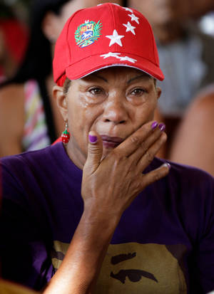 "Photo - A supporter of Venezuela's President Hugo Chavez wipes away tears as she prays for the ailing president at the military hospital's chapel in Caracas, Venezuela, Tuesday, March 5, 2013. A brief statement read on national television by Communications Minister Ernesto Villegas late Monday carried the sobering news about the charismatic 58-year-old leader's deteriorating health. Villegas said Chavez is suffering from ""a new, severe infection."" The state news agency identified it as respiratory. (AP Photo/Ariana Cubillos)"