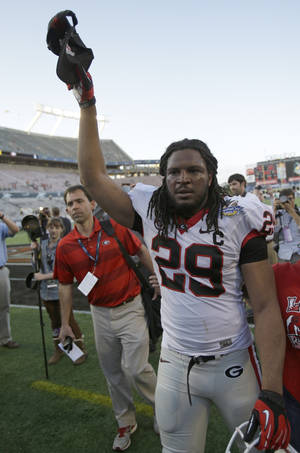 photo - Georgia linebacker Jarvis Jones tips his hat to fans as he leaves the field after defeating Nebraska 45-31 in the Capital One Bowl NCAA football game, Tuesday, Jan. 1, 2013, in Orlando, Fla. (AP Photo/John Raoux)