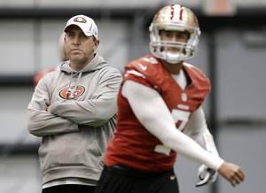 Photo - San Francisco 49ers quarterbacks coach Geep Chryst, left, watches as Colin Kaepernick (7) passes during practice on Wednesday, Jan. 30, 2013, in New Orleans. The 49ers are scheduled to play the Baltimore Ravens in the NFL Super Bowl XLVII football game on Feb. 3. (AP Photo/Mark Humphrey)