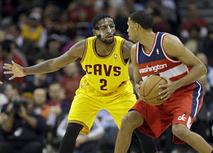 Photo - Cleveland Cavaliers' Kyrie Irving (2) guards Washington Wizards' Garrett Temple in the second quarter of an NBA basketball game on Wednesday, Nov. 20, 2013, in Cleveland. (AP Photo/Mark Duncan)