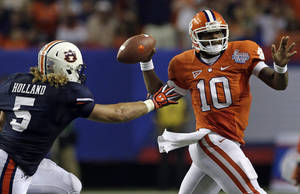 photo -   Clemson quarterback Tajh Boyd (10) looks for a receiver as he is pursued by Auburn linebacker Jake Holland (5) in the second half of a NCAA college football game at the Georgia Dome in Atlanta Saturday, Sept. 1, 2012. Clemson beat Auburn 26-19. (AP Photo/Dave Martin)