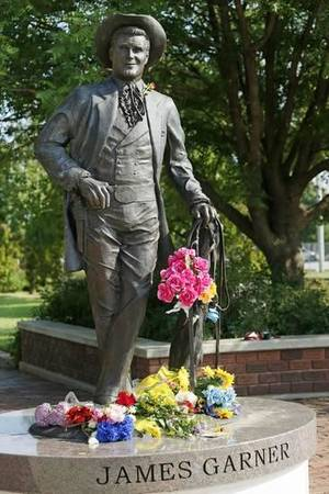 Flowers rest July 20 on the statue of James Garner on Main Street in downtown Norman. Garner died July 19 at age 86. Photo by Nate Billings, The Oklahoman Archive