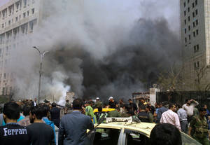 Photo - This photo released by the Syrian official news agency SANA, shows smoke rising from burned cars after a huge explosion shook the Sabaa Bahrat Square, one of the capital's biggest roundabouts, in Damascus, Syria, Monday, April. 8, 2013. A car bomb rocked a busy residential and commercial district in central Damascus on Monday, killing more than a dozen with many more injured and sending a huge cloud of black smoke billowing over the capital's skyline, Syrian state-run media said. (AP Photo/SANA)