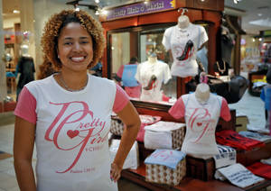 Photo - Yvonne Washington of Oklahoma City poses for a photo near her Pretty Girls 4 Christ kiosk at Quail Springs Mall . Washington showed off her line of Christian-themed T-shirts and jewelry at the kiosk during the Christmas holidays.  <strong>CHRIS LANDSBERGER - CHRIS LANDSBERGER</strong>