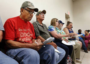 Photo -  David L. Burris, of Ada, Tony Tinsley, of Norman, and Gail and Jack Wilcox, of Norman, wait for assistance June 19 at Veteran's Corner in Goldsby. Photo by Steve Sisney, The Oklahoman  <strong>STEVE SISNEY -   </strong>